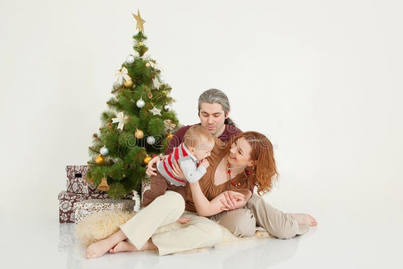 Famiglia felice che si siede all'albero del nuovo anno sullo studio bianco fotografia stock