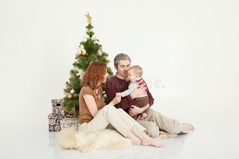Famiglia felice che si siede all'albero del nuovo anno sullo studio bianco immagine stock libera da diritti