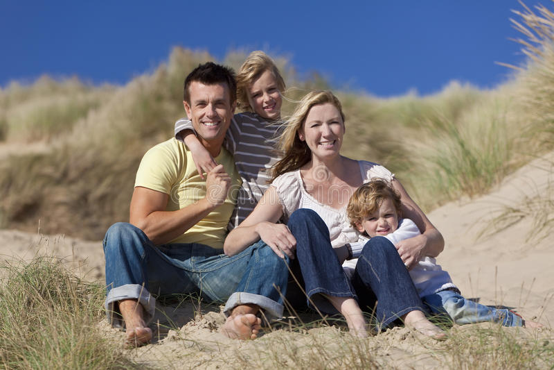 Famiglia felice che si siede avendo divertimento alla spiaggia fotografia stock libera da diritti