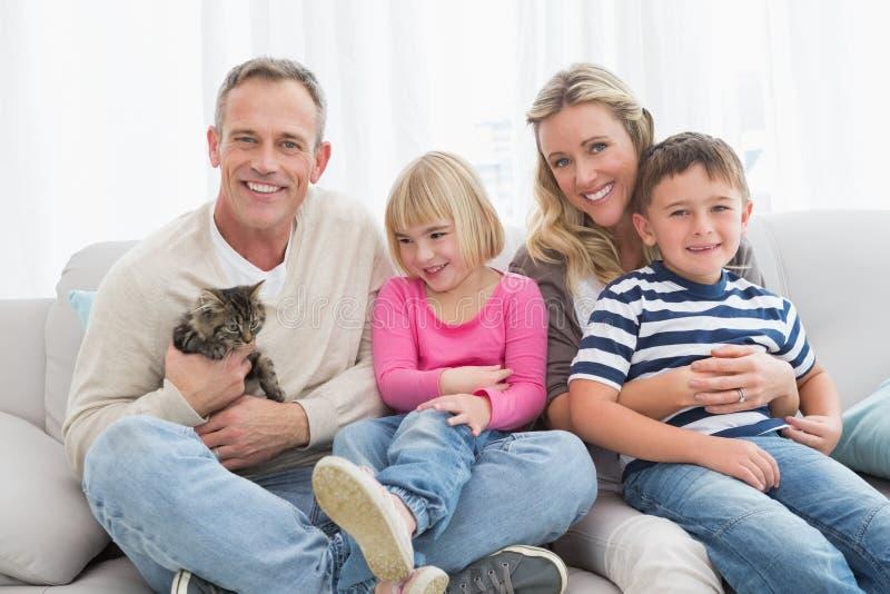 Famiglia felice che si siede insieme con il gattino dell'animale domestico immagine stock libera da diritti
