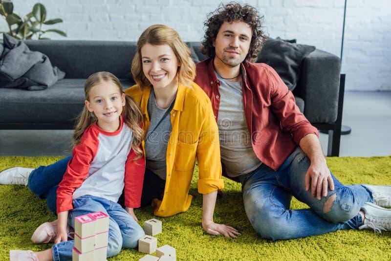 famiglia felice che si siede sul tappeto e che sorride alla macchina fotografica mentre giocando con i blocchi di legno fotografie stock