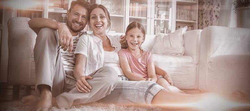 Famiglia felice che si siede sulla coperta in salone fotografia stock