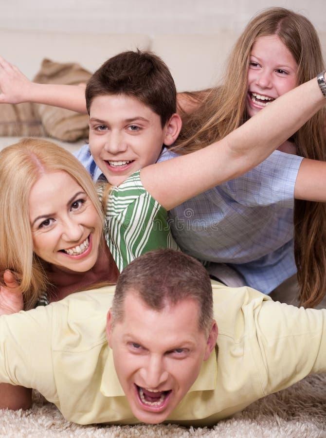 Famiglia felice che si trova in cima a vicenda immagine stock