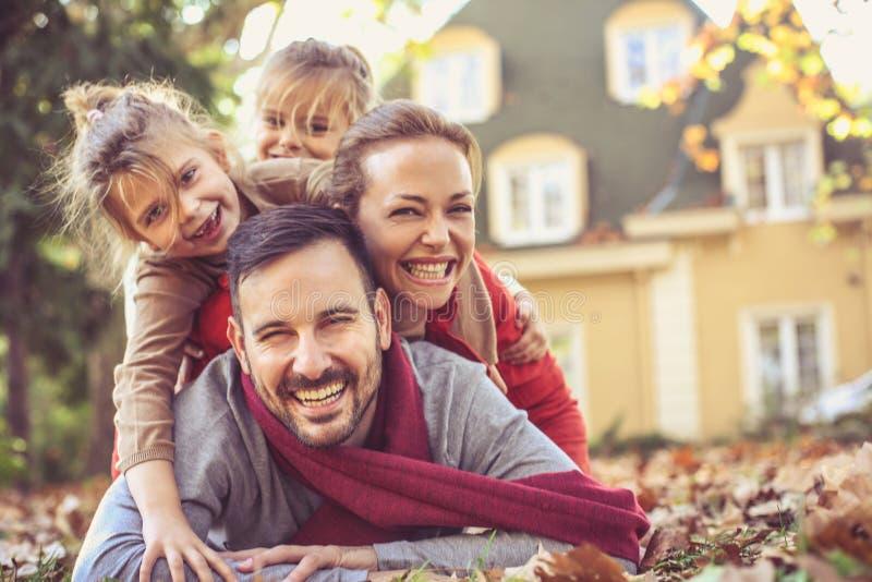 Famiglia felice che si trova in foglie di autunno fotografia stock