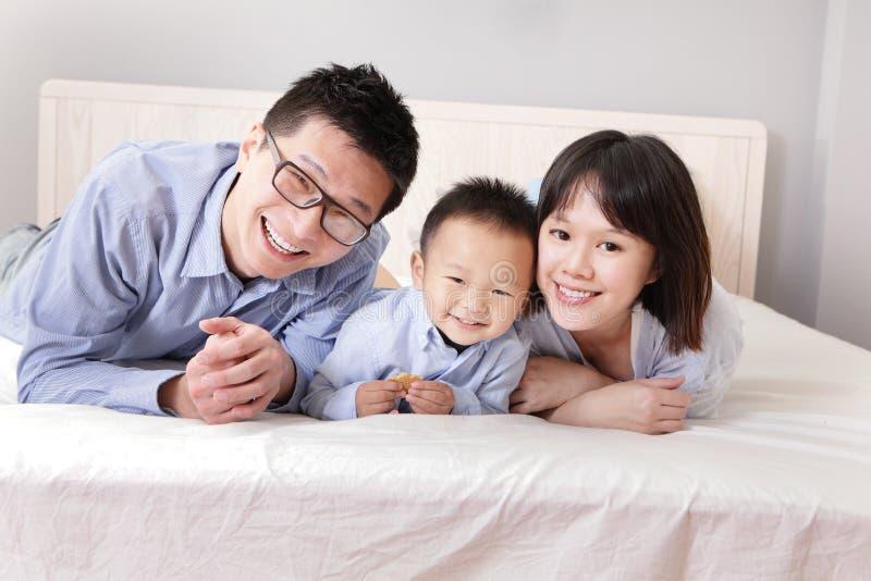 Famiglia felice che si trova sul letto immagini stock libere da diritti