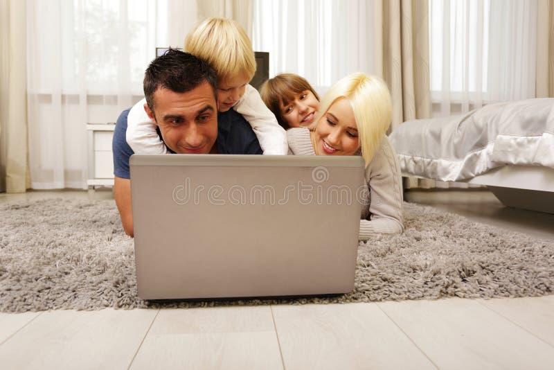 Famiglia felice che si trova sul tappeto e sul gioco immagini stock