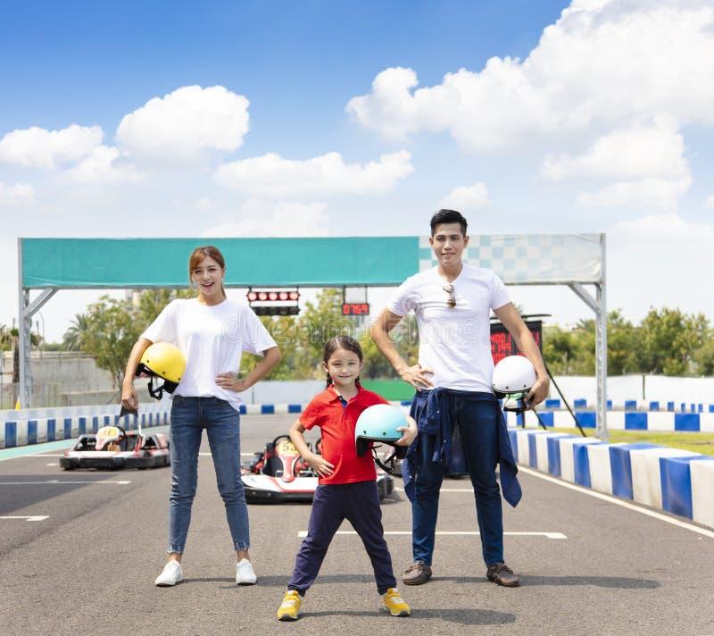 Famiglia felice che sta in movimento la pista di corsa del kart fotografie stock libere da diritti