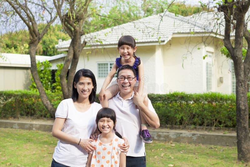 Famiglia felice che sta prima della loro casa immagine stock