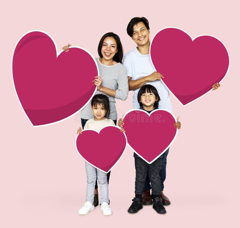 Famiglia felice che tiene le forme del cuore fotografia stock libera da diritti
