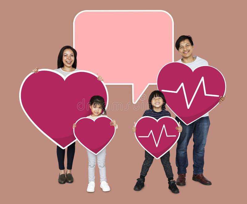 Famiglia felice che tiene le icone di un cuore di rosa illustrazione di stock