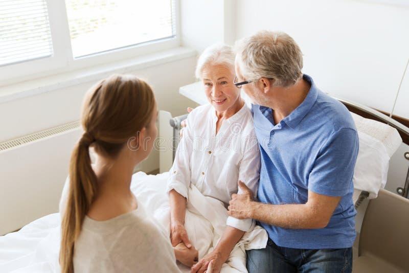 Famiglia felice che visita donna senior all'ospedale immagine stock