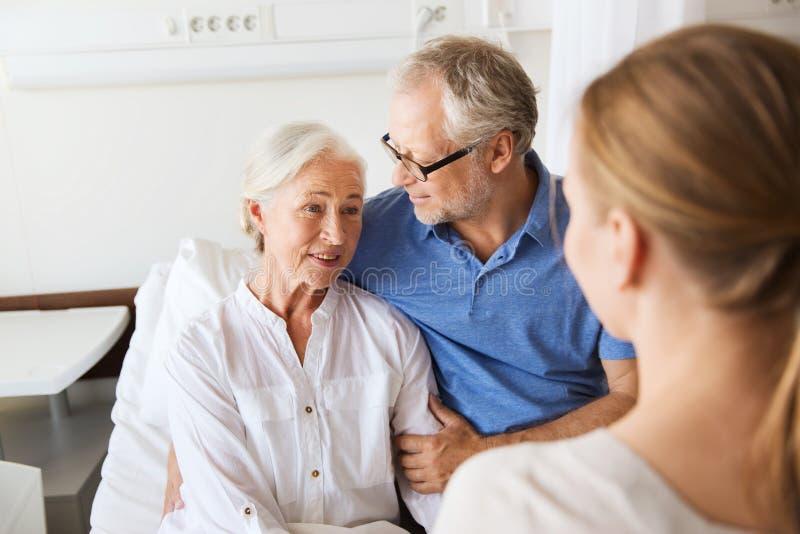 Famiglia felice che visita donna senior all'ospedale fotografie stock libere da diritti