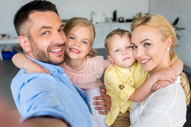 famiglia felice con due bambini che abbracciano e che sorridono alla macchina fotografica immagine stock