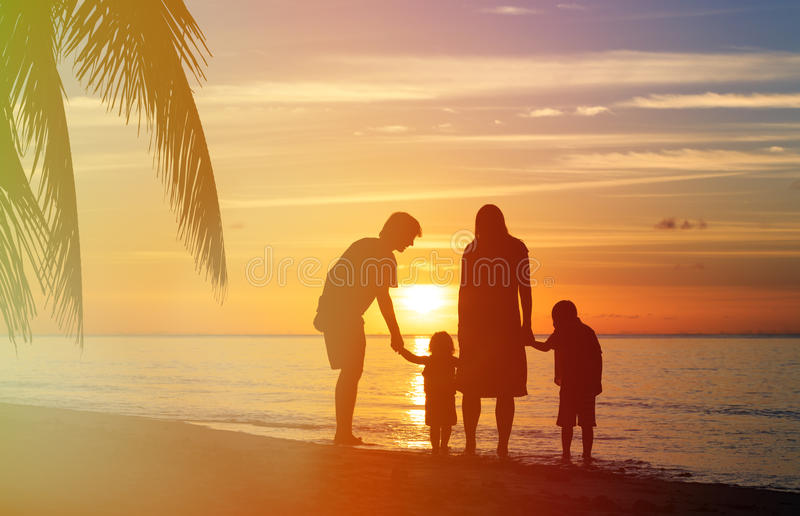 Famiglia felice con due bambini che camminano sulla spiaggia di tramonto immagine stock