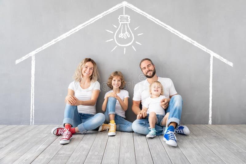 Famiglia felice con due bambini che giocano nella nuova casa immagini stock libere da diritti
