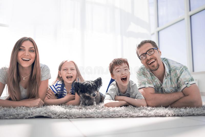 Famiglia felice con due bambini che si trovano nel nuovo salone fotografia stock libera da diritti