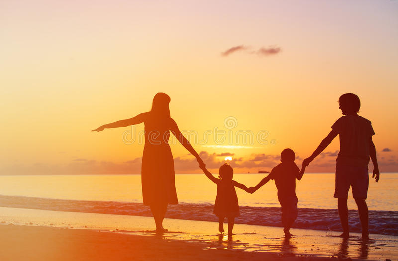 Famiglia felice con due bambini divertendosi al tramonto fotografia stock