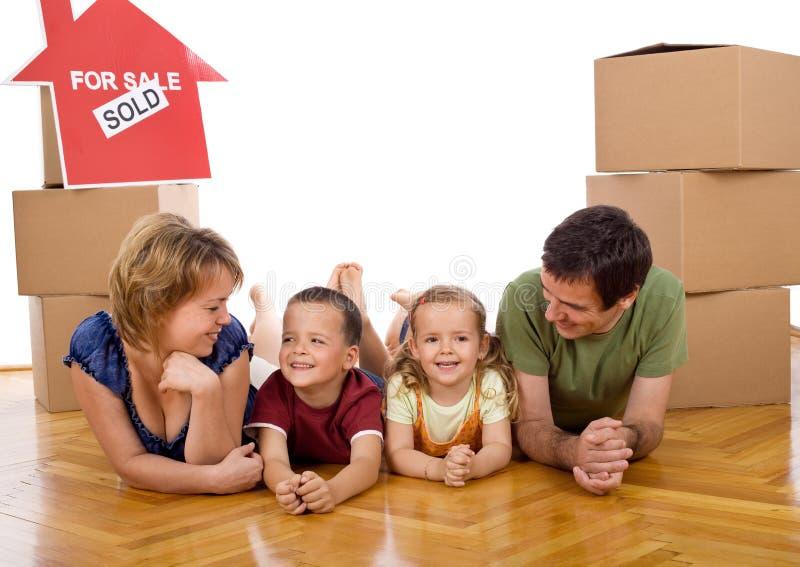 Famiglia felice con due bambini nella loro nuova casa fotografia stock