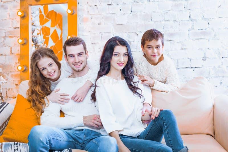 Famiglia felice con due bambini ragazzo e ragazza che si siedono sullo strato dentro fotografia stock libera da diritti