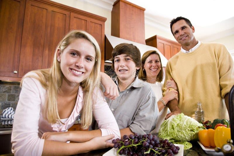 Famiglia felice con gli adolescenti in cucina immagini stock