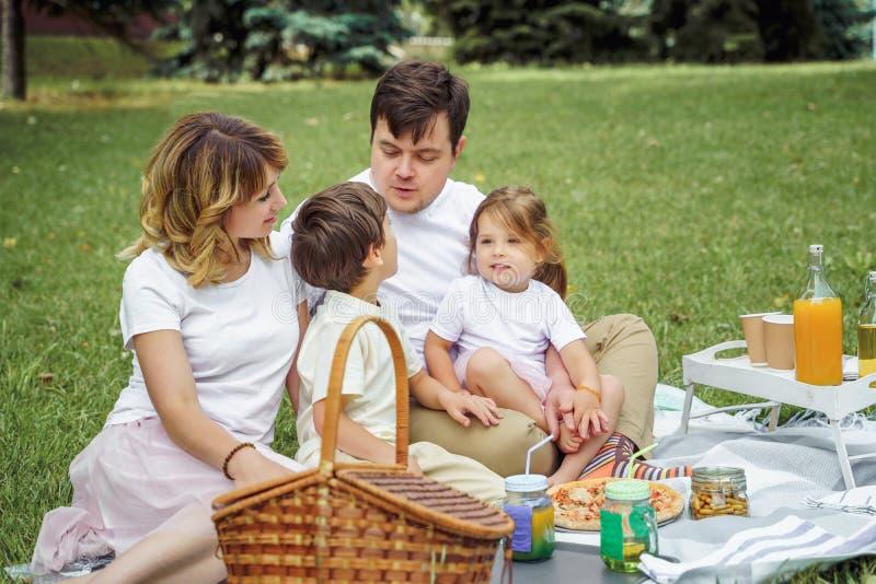 Famiglia felice con i bambini che riposano sull'erba durante il picnic Vita in famiglia di armonia e di felicit? fotografia stock libera da diritti