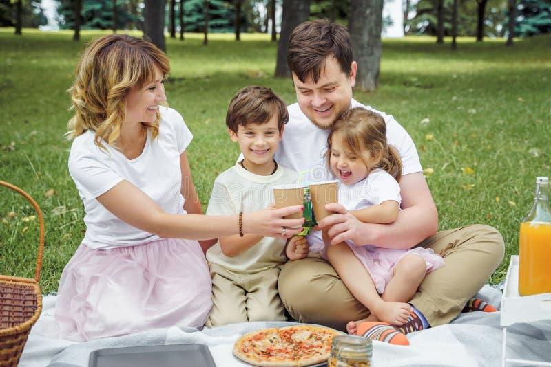 Famiglia felice con i bambini che riposano sull'erba durante il picnic Vita in famiglia di armonia e di felicit? fotografia stock