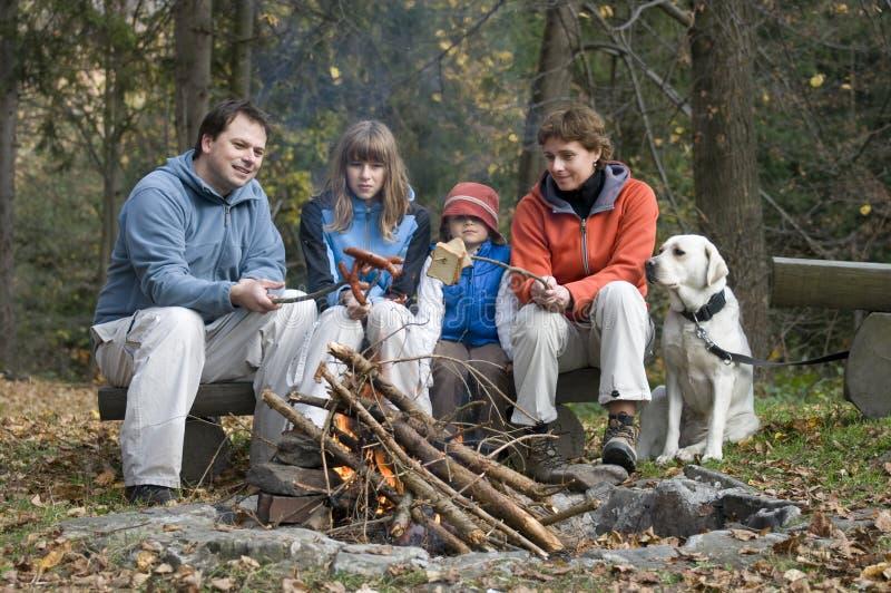 Famiglia felice con il cane vicino a fuoco di accampamento immagini stock libere da diritti