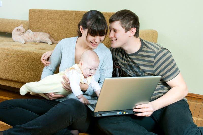 Famiglia felice con il computer portatile immagine stock