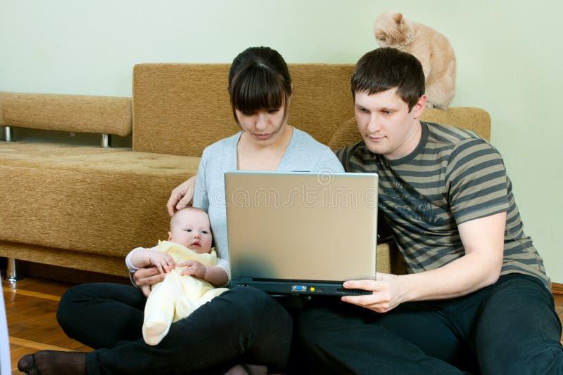 Famiglia felice con il computer portatile fotografia stock libera da diritti