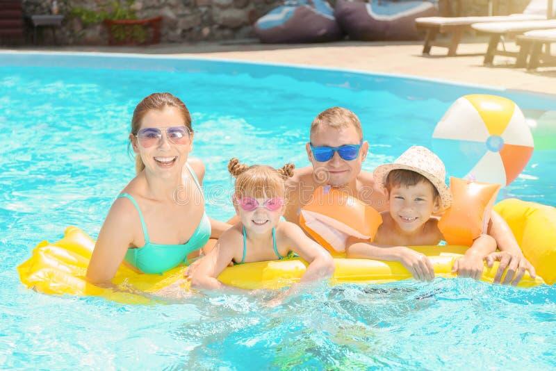 Famiglia felice con il materasso gonfiabile nella piscina fotografie stock