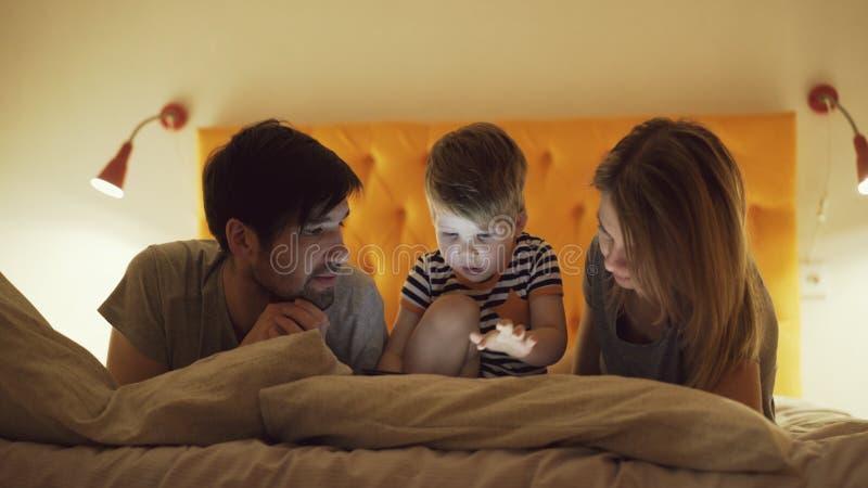 Famiglia felice con il piccolo figlio che impara giocare il computer della compressa che si trova a letto a casa nella sera fotografia stock