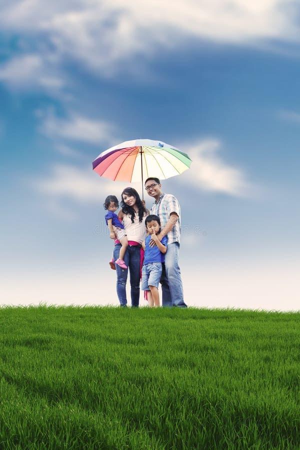 Famiglia felice con l'ombrello variopinto in prato fotografie stock libere da diritti