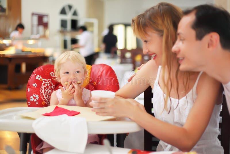 Famiglia felice con la bambina bionda che mangia pane immagini stock