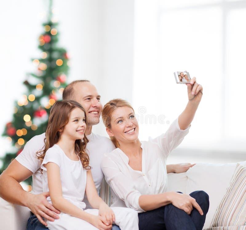 Famiglia felice con la macchina fotografica a casa fotografia stock