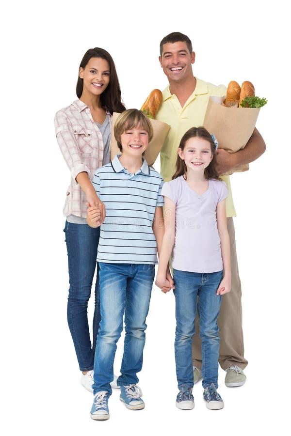 Famiglia felice con le borse di drogheria fotografia stock