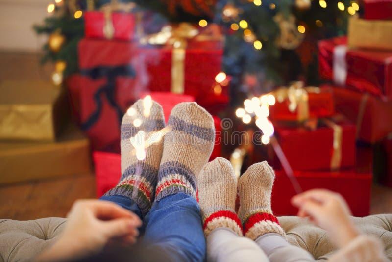 Famiglia felice con le luci di Bengala sopra i precedenti di Natale immagini stock