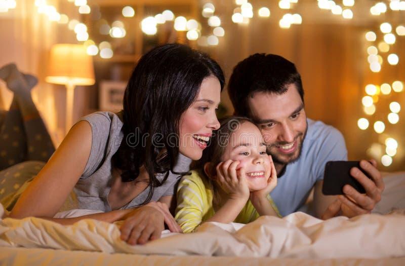 Famiglia felice con lo smartphone a letto alla notte immagini stock