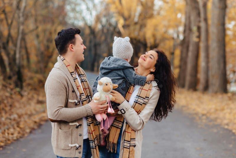Famiglia felice con poca passeggiata del bambino alla strada del parco con l'albero giallo fotografia stock