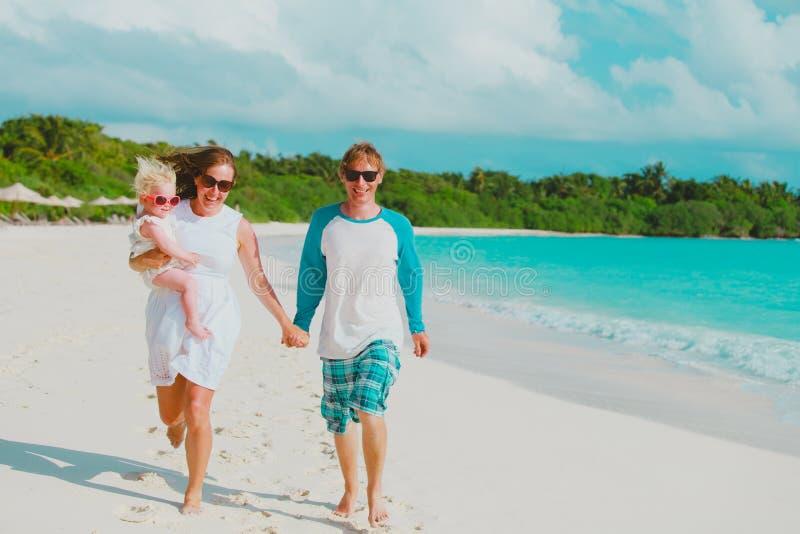 Famiglia felice con poco funzionamento del gioco della figlia del bambino sulla spiaggia fotografia stock libera da diritti