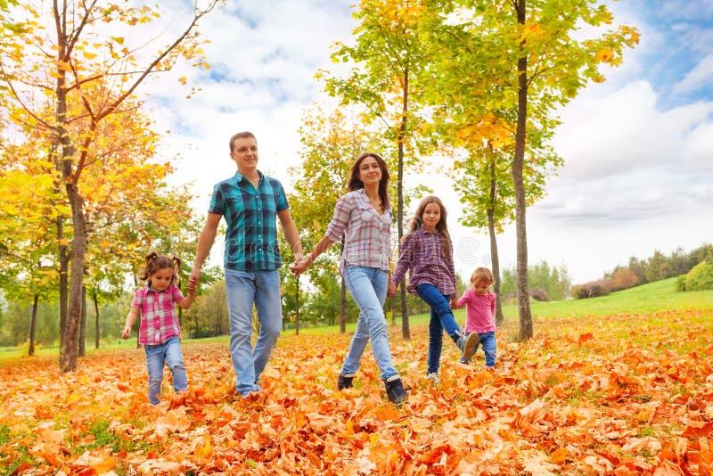 Famiglia felice con tenersi per mano della passeggiata di tre bambini fotografie stock libere da diritti