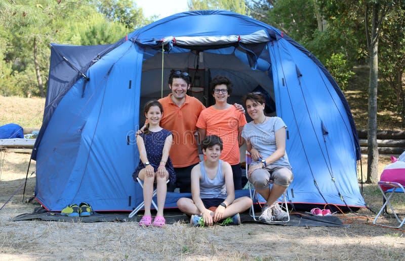 Famiglia felice con tre bambini e tende sorridenti nel campeggio estivo immagine stock libera da diritti