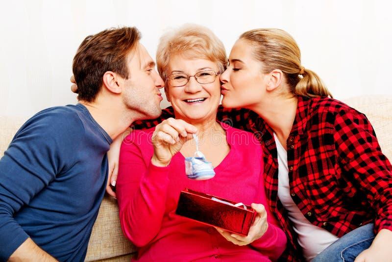 Famiglia felice - coppia con la donna anziana che contenitore di regalo della tenuta e scarpa di bambino immagini stock libere da diritti