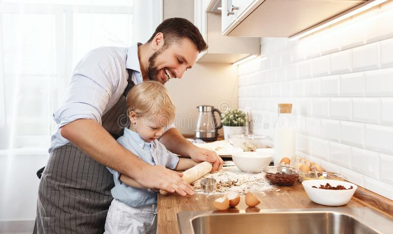 Famiglia felice in cucina biscotti di cottura del bambino e del padre fotografia stock