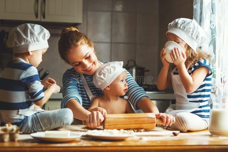 Famiglia felice in cucina madre e bambini che preparano pasta, sedere fotografia stock libera da diritti