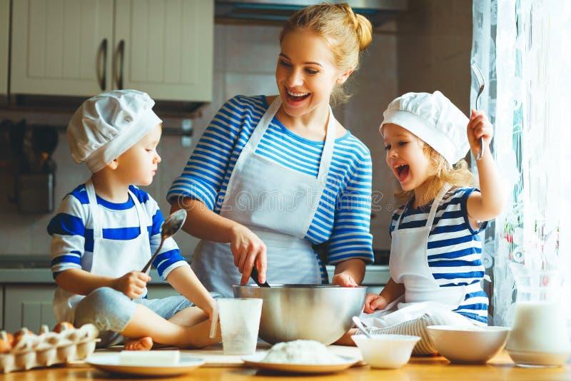 Famiglia felice in cucina madre e bambini che preparano pasta, sedere immagine stock