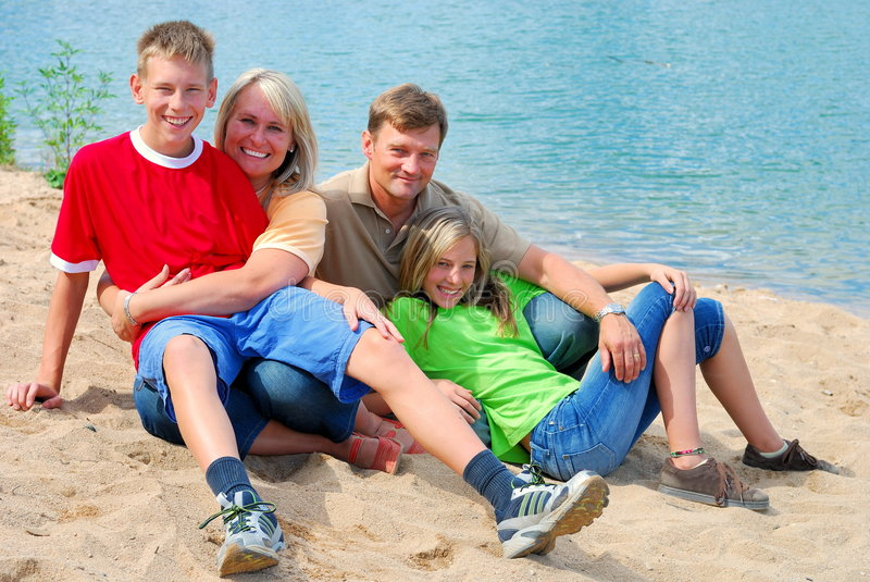 Famiglia felice dal lago fotografia stock