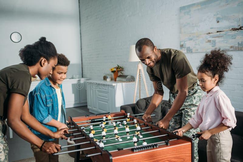 Famiglia felice dei genitori del soldato e di gioco afroamericano dei bambini fotografie stock