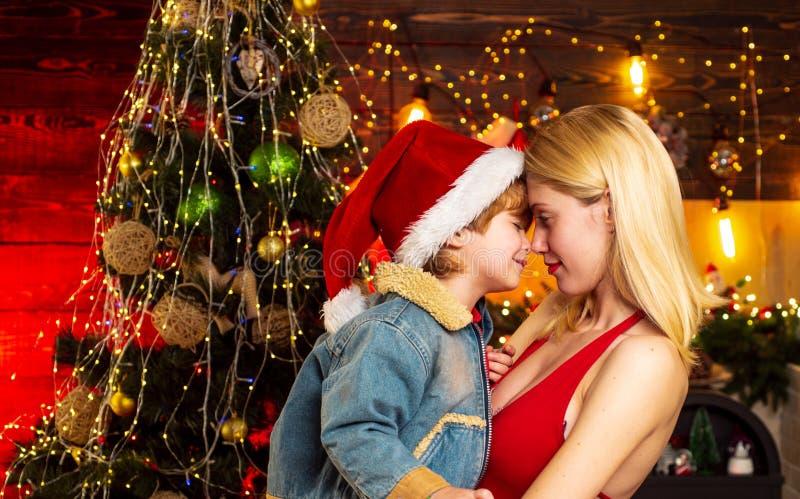 Famiglia felice del ritratto giovane Buon Natale e buon anno La madre tiene in armi, abbraccio tenero, delicatamente abbraccia il immagine stock