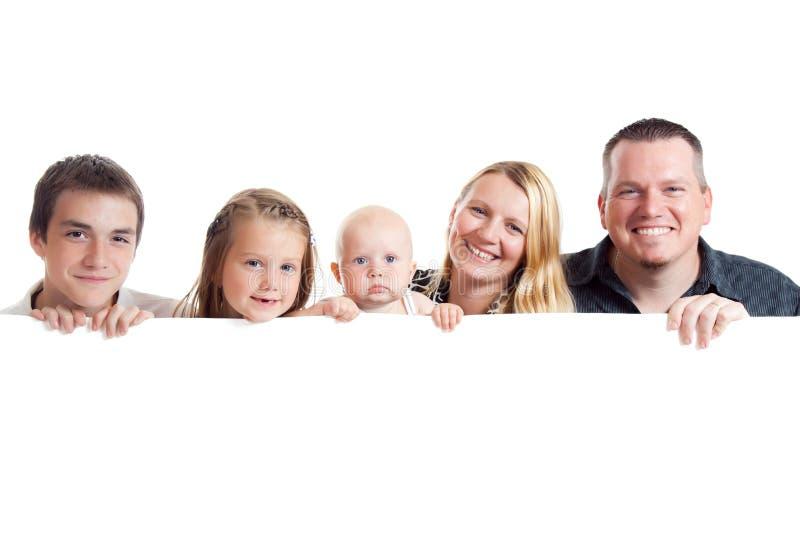 Famiglia felice dietro la scheda bianca fotografia stock libera da diritti