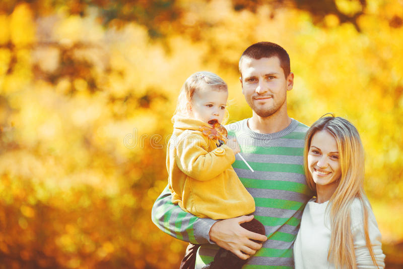 Famiglia felice divertendosi all'aperto in autunno nel parco immagini stock libere da diritti